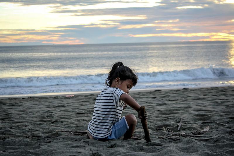 Full length of boy on beach against sky during sunset