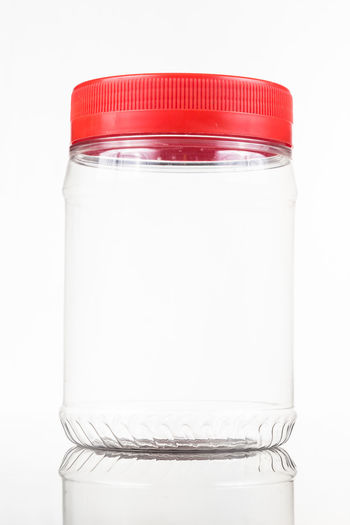 Plastic jar bottle with red cover lid against white background Bottle Close-up Container Copy Space Cover Cut Out Food And Drink Glass - Material Healthcare And Medicine Indoors  Jar Lid No People Plastic Polyurethane Red Color Single Object Still Life Studio Shot Transparent White Background White Color