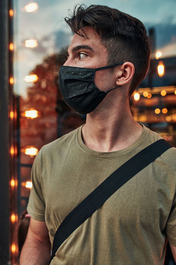 Young man wearing mask looking away outdoors