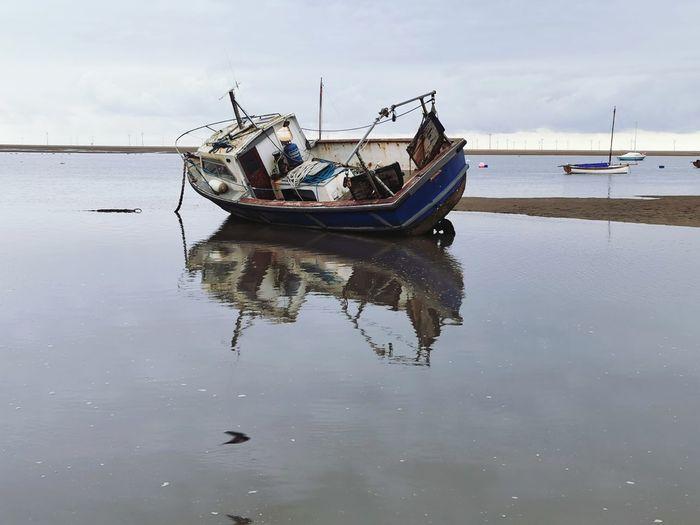 Fishing boat moored in sea against sky