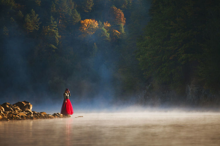 Woman standing at lakeshore in forest during foggy weather