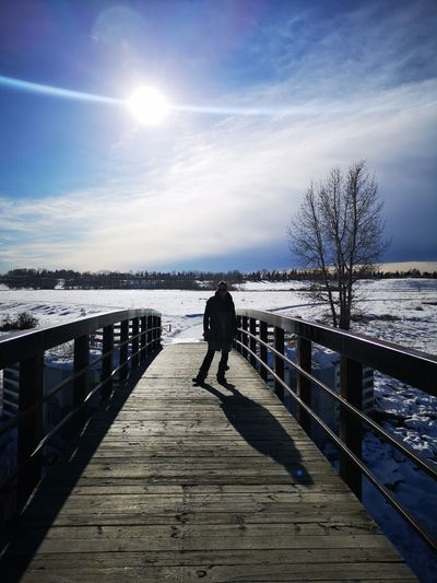 Man on railing against sky during winter