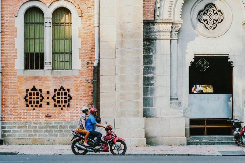Three people riding moped on city street