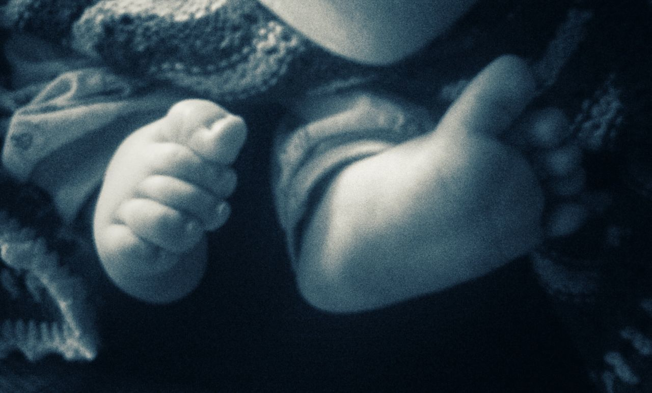 LOW SECTION OF BABY FEET IN HANDS