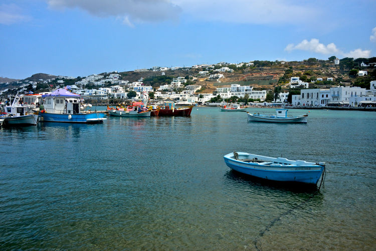 panoramic view of port of Mykonos with colored fishing boats moored and cityscape behind with white buildings Nautical Vessel Water Transportation Mode Of Transportation Sea Architecture Sky Building Exterior Moored Waterfront Built Structure City Harbor Cloud - Sky Nature Day No People Building Travel Outdoors Yacht Sailboat Anchored Passenger Craft Yachting Boats Fishing Boat Seascape Mykonos,Greece Panoramic View Colored Boats Travel Destinations Panorama Beauty In Nature Travel Summertime Turquoise Colored Landscape Seaside Seafront City Marina Bay
