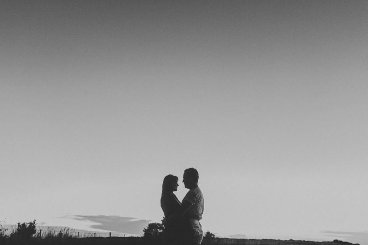 Silhouette couple embracing while standing against clear sky