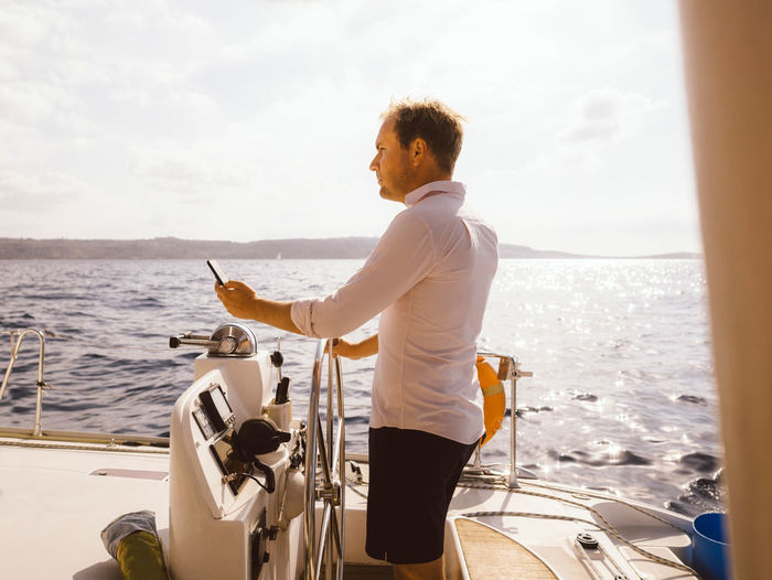 Man holding boat in sea against sky