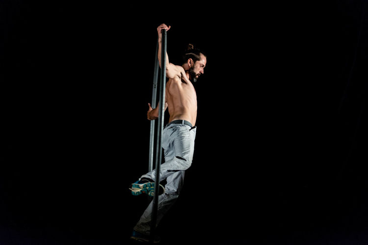 Circus Adult Black Background Casual Clothing Copy Space Full Length Holding Indoors  Jeans Men Night One Person Side View Sport Standing Strength Studio Shot Young Adult Young Men