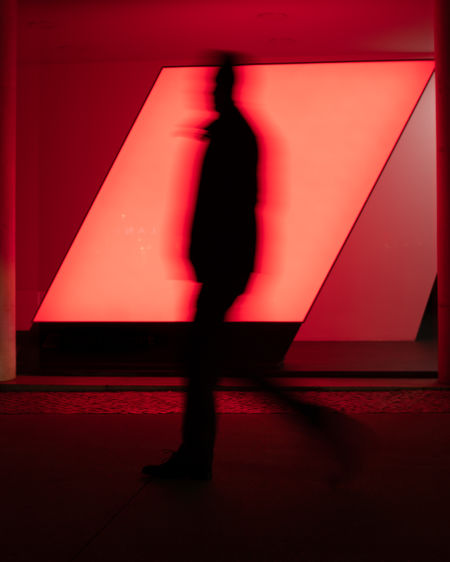 Blurred motion of silhouette man walking in corridor