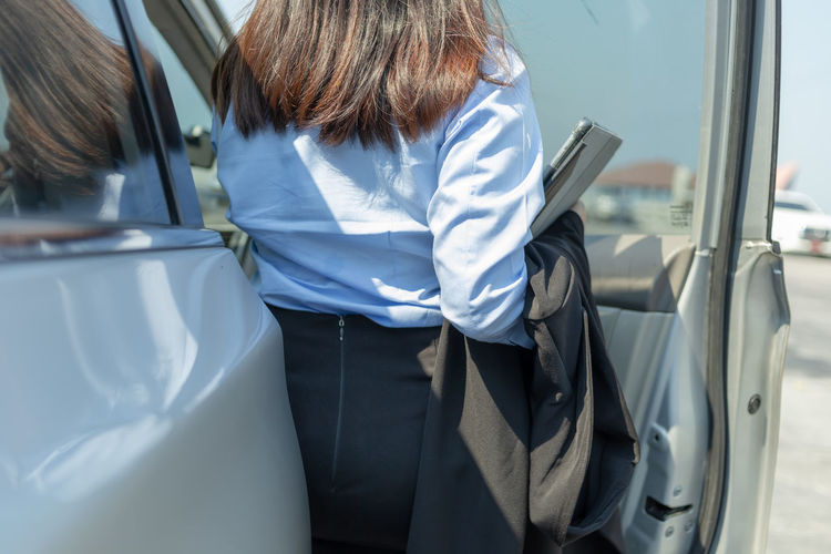 Midsection of businesswoman standing by car