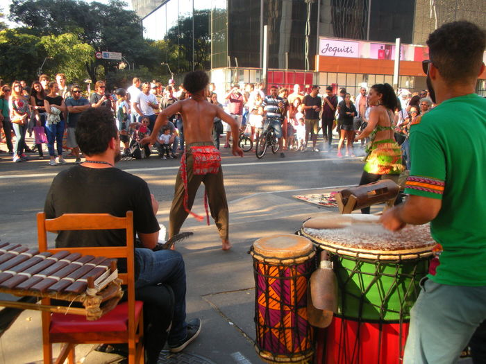 July 15, 2018 - On Sunday Avenida Paulista is closed off to traffic. This is the day when people take to the street to relax, exercise, walk, jog, ride bicycles, listen to music, have a snack and soak up the sun. In this photo, outdoor Brazilian musicians perform a tropical beat to a crowd of people on Avenida Paulista. Avenida Paulista City Life Dancing Drummer Financial District  Street Dancers Susan A. Case Sabir The Photojournalist - 2018 EyeEm Awards The Street Photographer - 2018 EyeEm Awards Unretouched Photography Celebration City City Planning Downtown São Paulo Drums Large Group Of People Leisure Activity Outdoor Music Real People Street Dancing Street Music Street Musicians Sunny Day Tropical Music Urban Landscape
