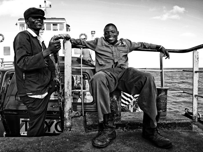 Real People Men Two People Males  Sitting Looking At Camera Full Length Casual Clothing Young Men Portrait People Day Mode Of Transportation Young Adult Occupation Transportation Standing Smiling Mature Men Sky Outdoors Uniform