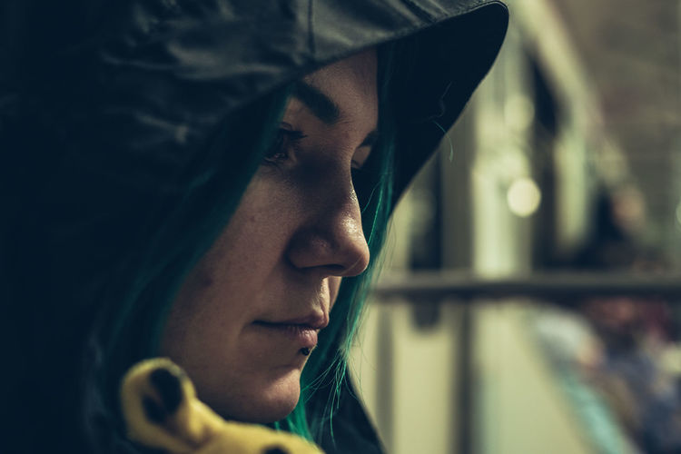 Close-up of thoughtful woman wearing hood sitting in vehicle