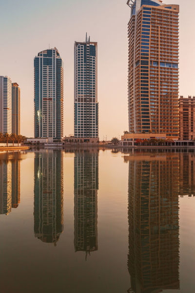 Sunset time in Dubai Dubai JLT Reflection UAE UAE , Dubai Architecture Building Exterior Built Structure City Day Dubaicity Modern No People Outdoors Reflecting Pool Reflection Reflection_collection Reflections Sky Skyscraper Symmetry Travel Destinations Urban Skyline Water Waterfront
