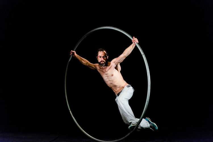 Circus Acrobat Arts Culture And Entertainment Balance Black Background Exercising Flexibility Front View Full Length Holding Human Arm Indoors  Lifestyles One Person Performance Plastic Hoop Real People Skill  Strength Studio Shot Young Adult