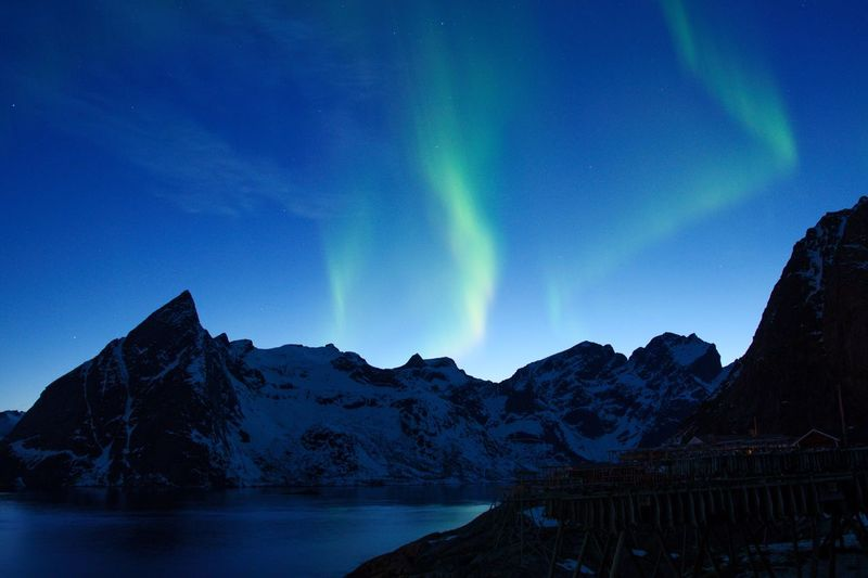 Green Aurora behind snow capped mountain in dark blue clear sky Snow Capped Mountains Snow Green Aurora Aurora Natural Phenomenon Natural Beauty Green Light Blue Sky Norway Northern Lights Mountain Sky Scenics - Nature Beauty In Nature Water Night Environment Mountain Range Tranquil Scene Star - Space Nature Lake Astronomy Tranquility Blue Landscape Space No People Idyllic Space And Astronomy