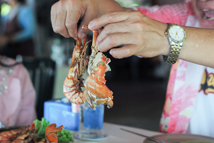 Closeup hands of man holding the steamed shrimp and clap.