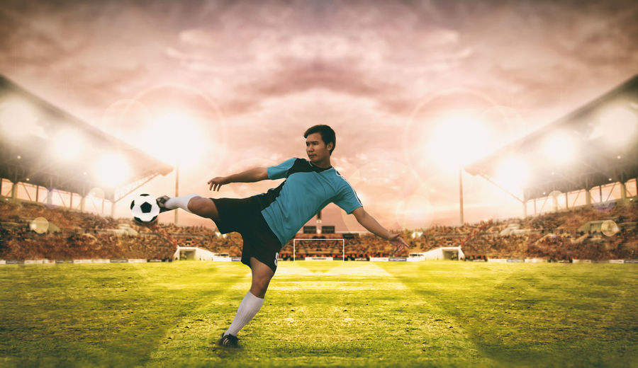 Digital composite image of soccer player kicking ball on field against sky