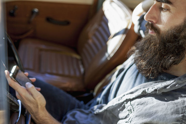 Bearded young man in vintage car using his smartphone