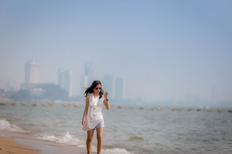 Mid adult woman wearing sunglasses walking at beach against clear sky