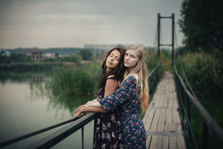 Lesbian couple embracing on footbridge against sky