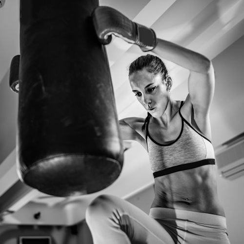 Woman practicing with punching bag in boxing rink