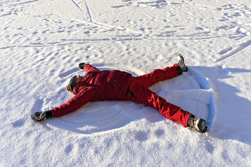 Young man in red winter clothes lying in the snow and making a snow angel. winter fun, christmas