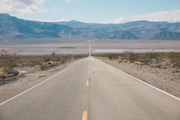 Empty road by desert against sky