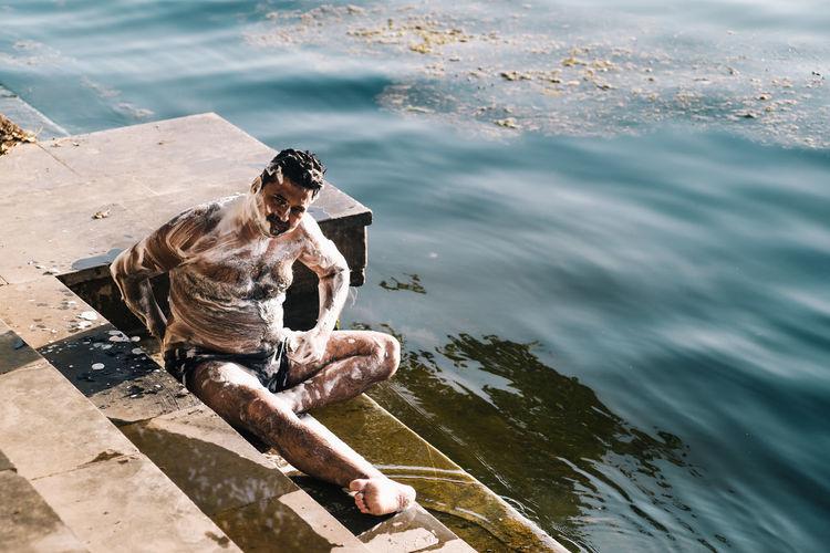 High angle view of man sitting at sea shore