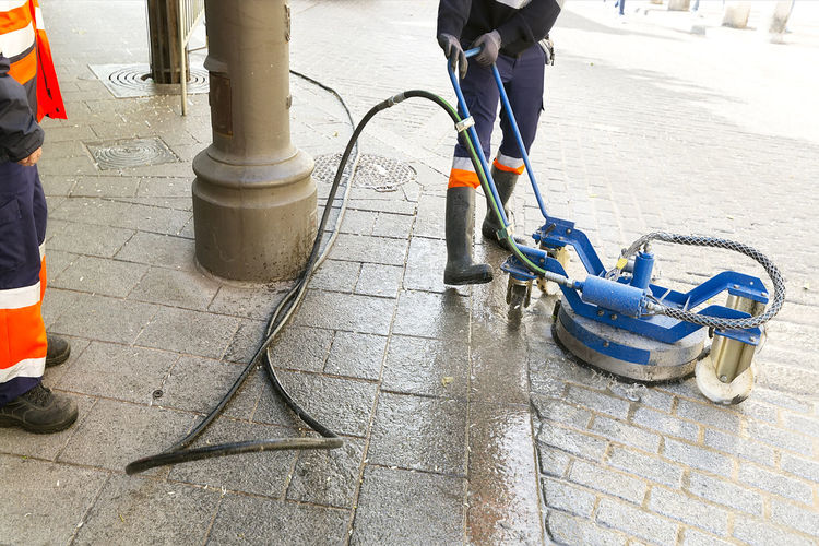 power water washing by worker of professional service in city street City Street Cleaning Equipment Power Service Washing Worker Cleaning Workers Dirty Footpath Human Body Part Human Leg Low Section Maintenance Men Municipality Outdoors Power Water Professional Real People Repair Restore Sidewalk Street Water