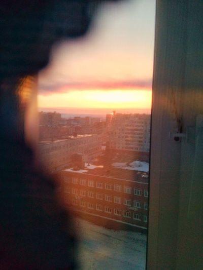 Cityscape seen through window at sunset