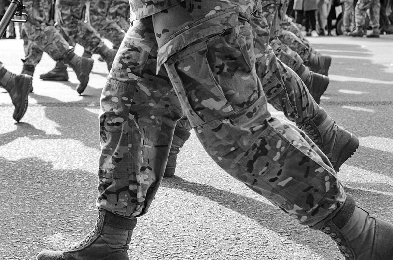 Low section of army soldier walking in city