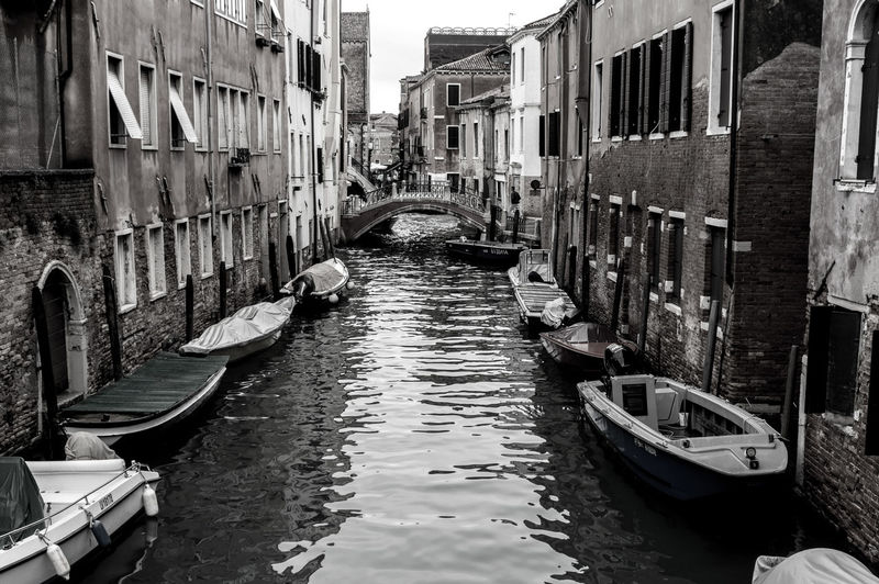 Boats moored in canal amidst buildings in city