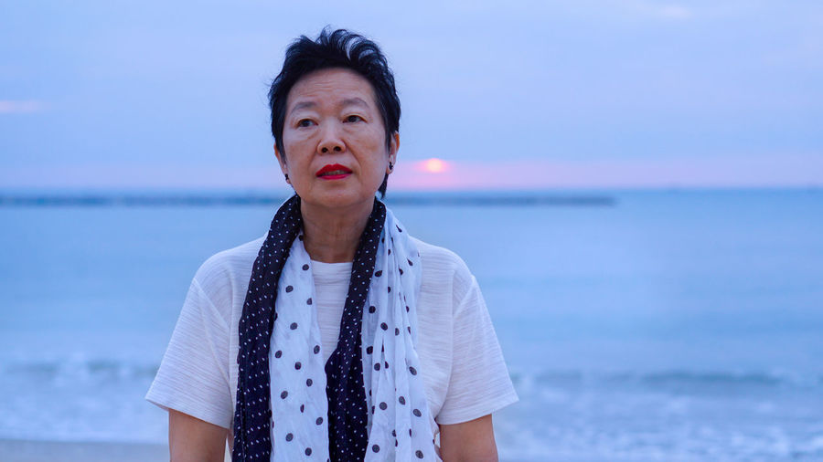 Thoughtful senior woman standing at beach against sky during sunset