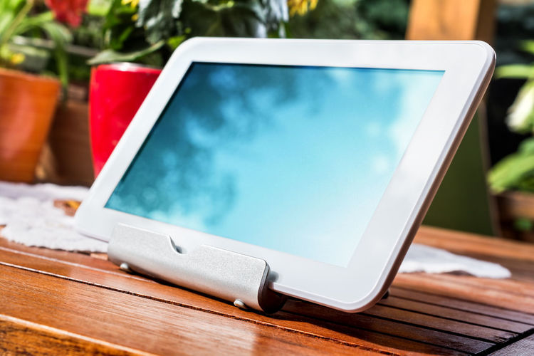 White Business Tablet On A Stand In Relaxing Atmosphere Autumn Bright Business Patio Reflection Standing Sunlight Sunny Tablet Wood Work Blank Close-up Colorful Computer Flowerpots Garden Homework Metal Outdoors Portable Sky Spring Table Wireless