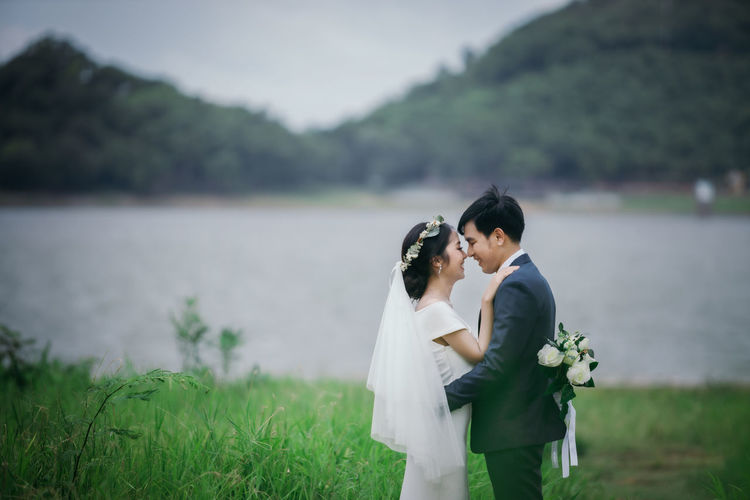 Married couple embracing amidst grass against lake