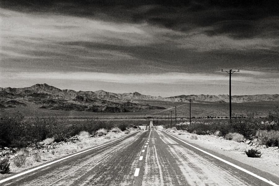 On the way to Jackson Hole, WY somewhere in the Mojave National Preserve in California ! The wide open road pure freedom! Deserts Around The World Monochrome Black And White Blackandwhite Landscape_Collection EyeEm Nature Lover On The Road Depth Of Field Straight Road Road Roadtrip