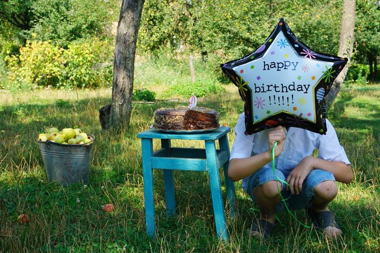 Boy holding balloon with happy birthday text while crouching by cake in park