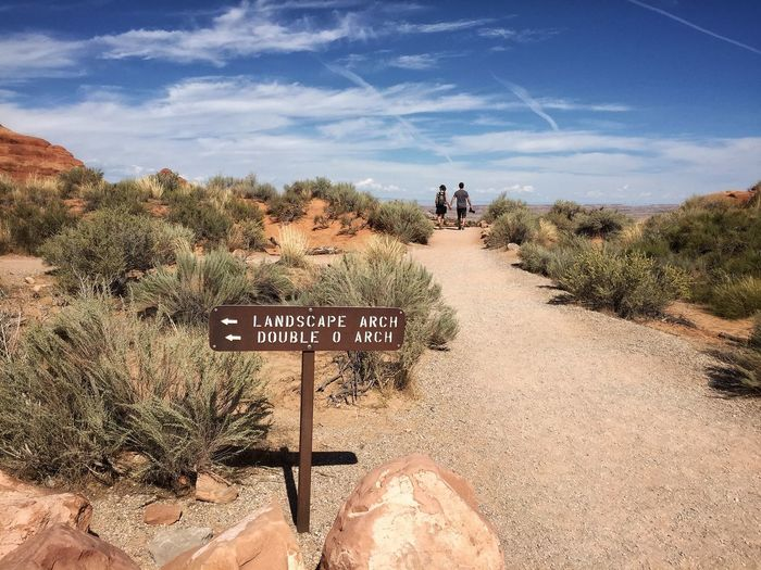 Rear view of men walking on footpath with directional sign in arches national park against sky