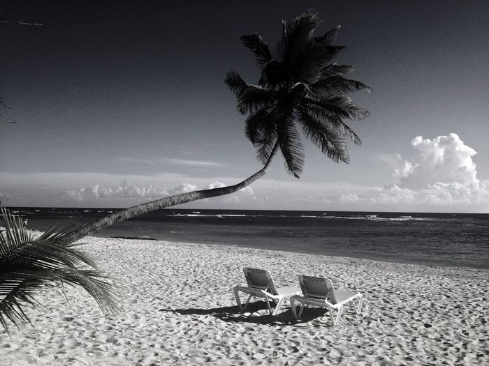 Lounge chairs at beach against sky