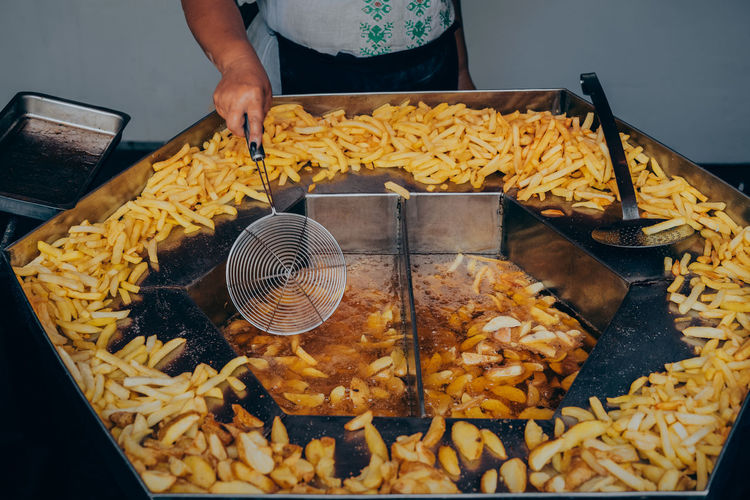 Midsection Of Man Preparing French Fries
