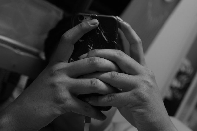 Close-up of man using phone in room