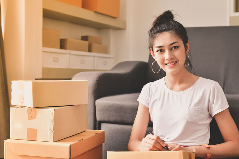Box Box - Container Cardboard Cardboard Box Casual Clothing Container Emotion Front View Happiness Home Interior Home Ownership Indoors  Lifestyles Looking At Camera One Person Packing Portrait Smiling Women Young Adult Young Women