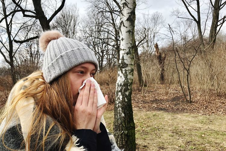 Close-up of teenage girl blowing nose while standing in forest
