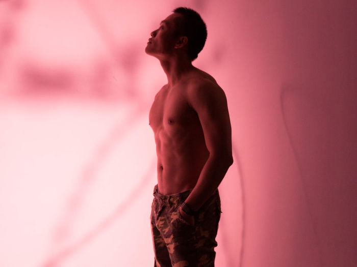 Side View Of Shirtless Man Standing Against Pink Background