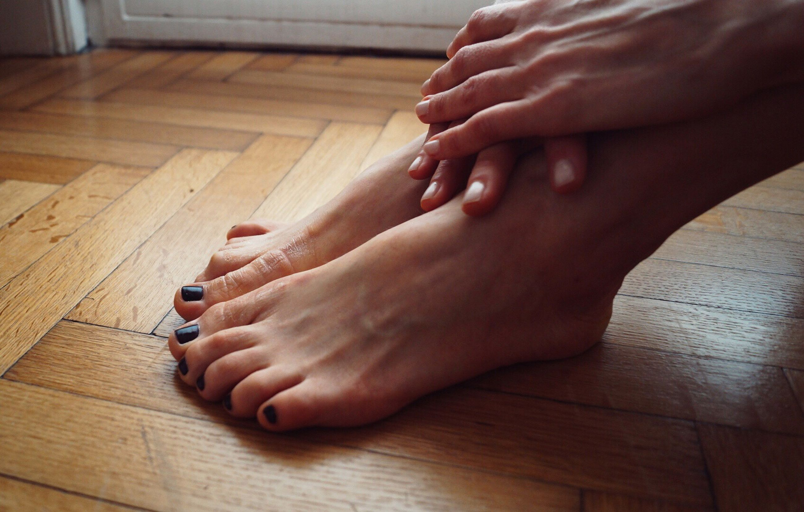 human body part, body part, barefoot, human leg, indoors, human foot, low section, real people, women, wood, flooring, adult, human hand, lifestyles, wood - material, hardwood floor, people, relaxation, hand, human limb, nail, finger, toenail, human toe