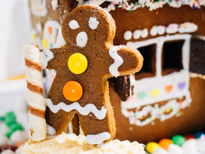 Close-up of gingerbread man and house at home