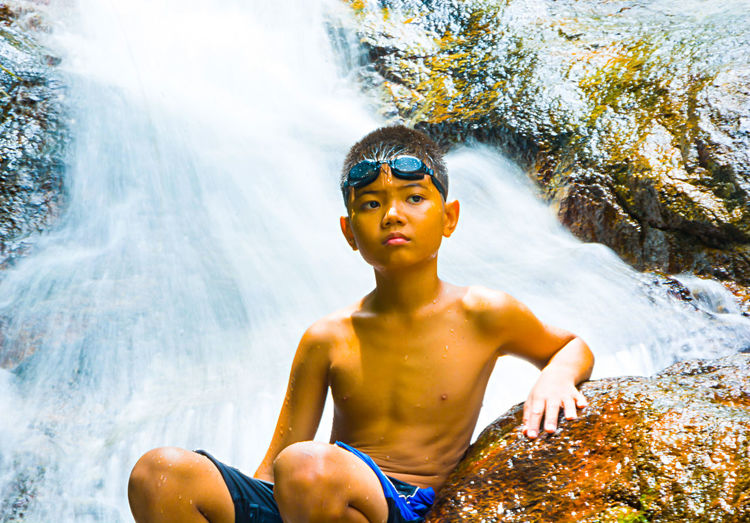 Shirtless Boy Sitting By Rock Against Waterfall