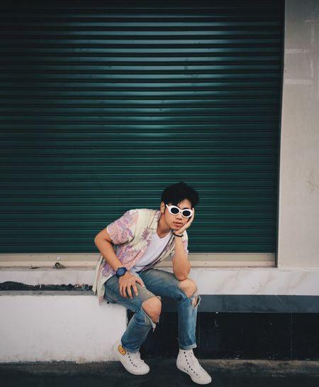 Portrait of man sitting against closed green shutter