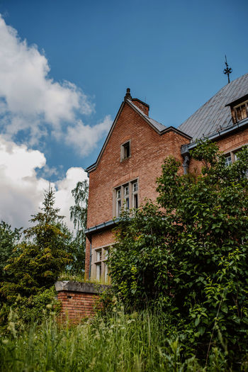 Low angle view of house and trees against sky